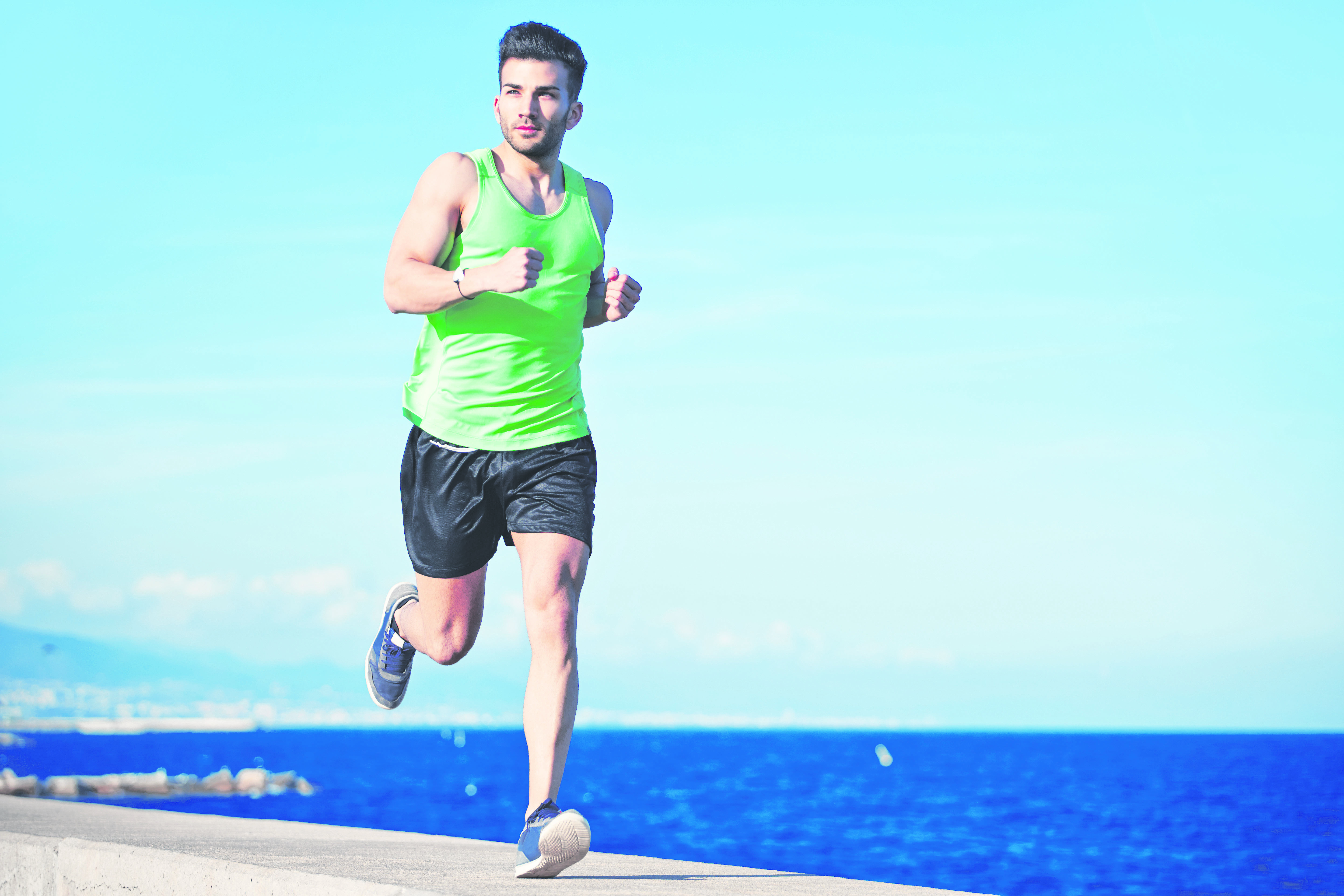 Attractive strong athlete running along the sea at evening